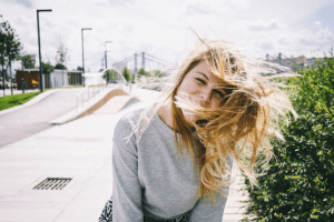 A girl wearing a grey sweatshirt smiling in the wind as her hair covers her face
