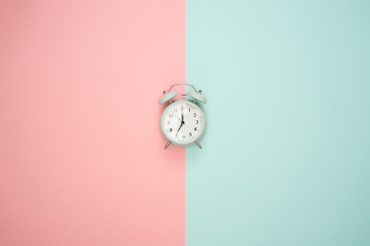 Clock atop a cotton candy split background.